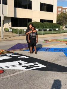 """Woman and child standing on the painted """"Black Lives Matter"""" street mural in Indianapolis."""